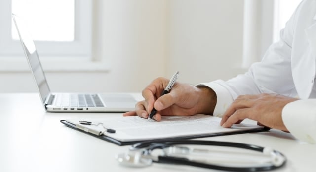 doctor writing down progress notes