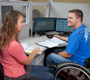 180 Medical employee sitting at a desk with another employee in a wheelchair