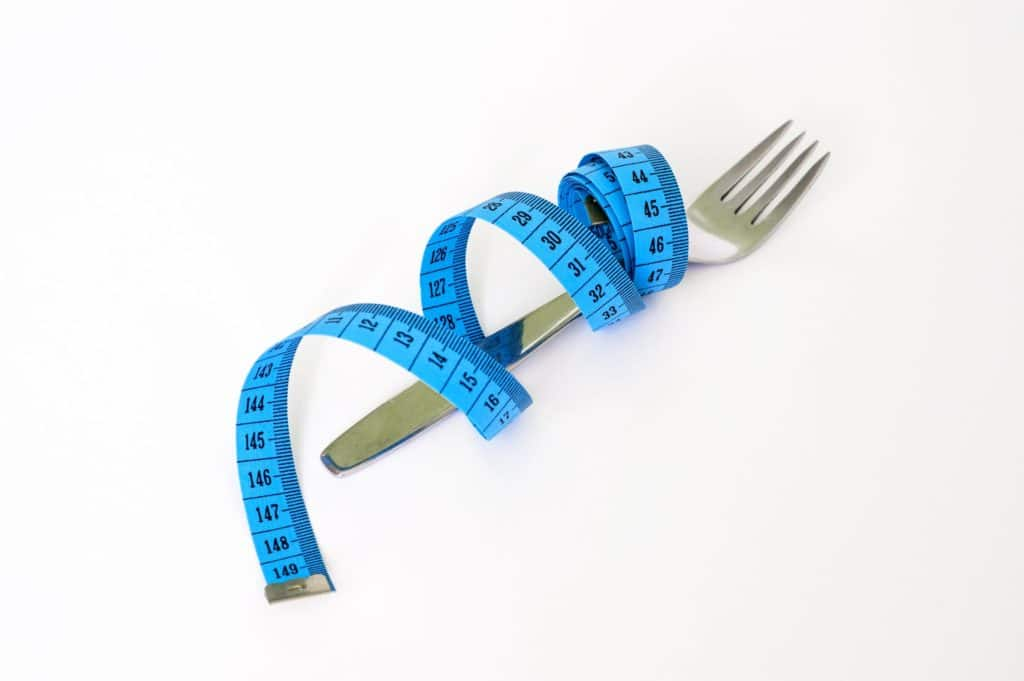 fork with measuring tape twirled around it