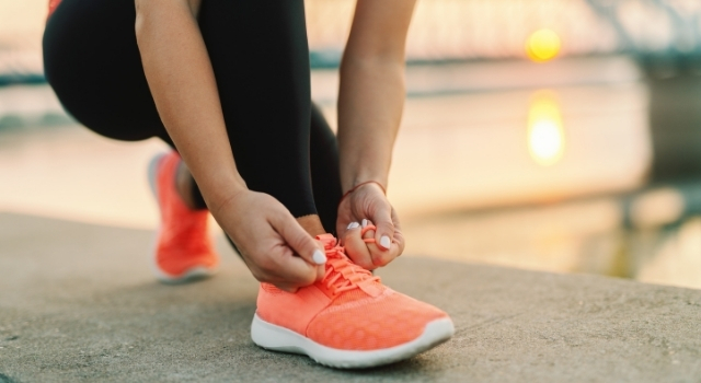 person lacing up orange shoes to go walking
